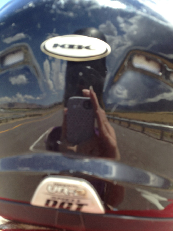 Elise does not take pictures of herself in the mirror. Instead she takes pictures of herself in reflections of my helmet, driving about 65 MPH.